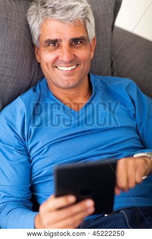 overhead portrait of mature man using tablet computer while lying on sofa