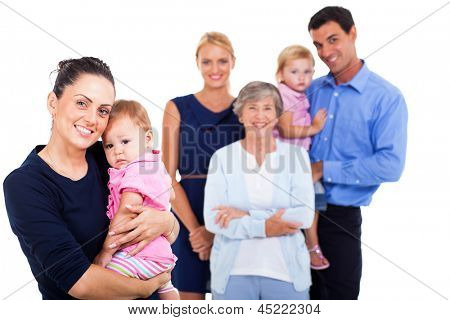 portrait of young woman holding her baby with extended family on background