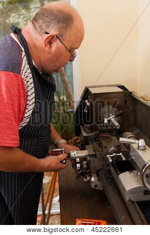 senior man using industrial lathe machine