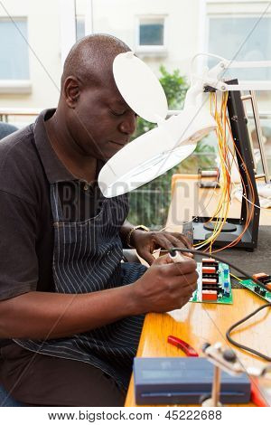 senior african technician repairing a circuit board under electronic magnifying glass