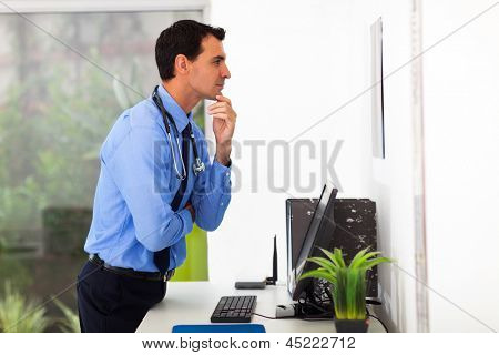 male doctor looking at the medical chart in office