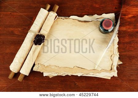 Old paper, ink, scrolls and feather on wooden background