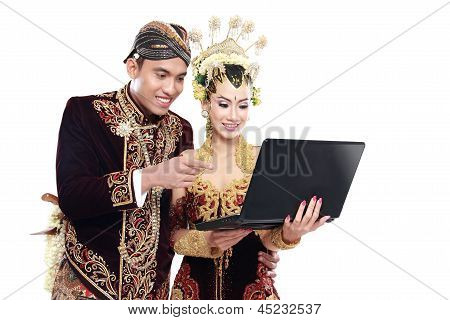 Happy Traditional Java Wedding Couple With Laptop