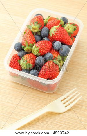 Healthy lunch box with strawberry and blueberry mix in office