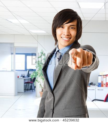 Portrait of a smiling asian businessman pointing his finger at you