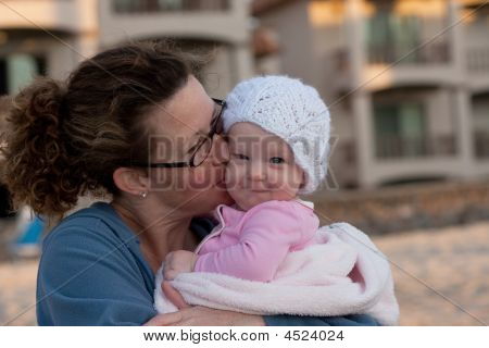 Baby Daughter Getting A Kiss From Mom
