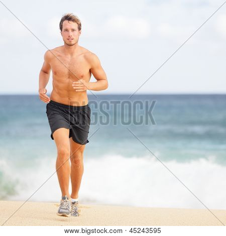 Running man jogging on beach. Male runner training outside working out. Fit young male sport fitness model exercising in full body in summer. Handsome strong caucasian man in his twenties.