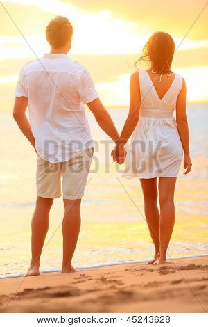 Young couple holding hands at beach sunset enjoying romance and sun. Young happy couple in love on romantic summer holidays vacation. Young lovers in casual clothing. Asia woman, Caucasian man.