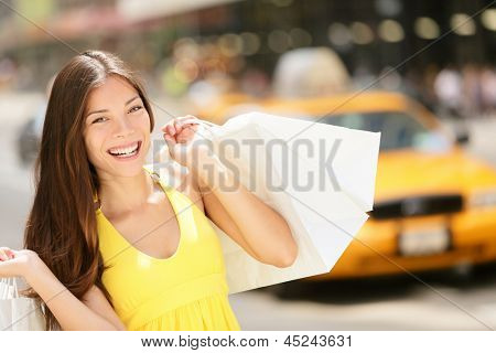 Happy shopper woman holding shopping bags, New York City, Manhattan, USA. Beautiful fresh joyful female model walking in street in summer dress with yellow taxi cab in background. Multiracial girl.