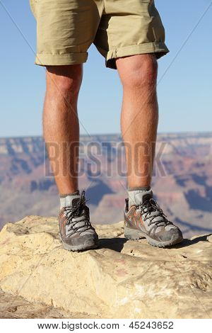 Hiking shoes on hiker in Grand Canyon. Man hikers hike boots in closeup with breathtaking view of Grand Canyon in the background. Male feet.