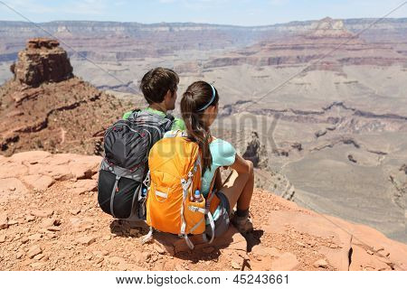 Hikers in Grand Canyon enjoying view of nature landscape. Young couple hiking relaxing during hike on South Kaibab Trail, south rim of Grand Canyon, Arizona, USA.