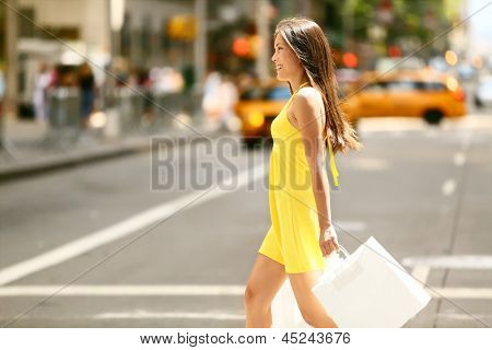 Shopping woman walking outside in New York City holding shopping bags. Shopper smiling happy crossing the street outdoors while on travel on Manhattan, United States. Beautiful model in summer dress.