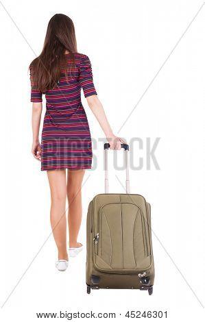 Vista posterior de poca mujer con maleta verde. hermosa chica morena en movimiento.  vista de la parte trasera