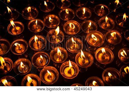 Burning candles in Tibetan Buddhist temple. Himachal Pradesh, India