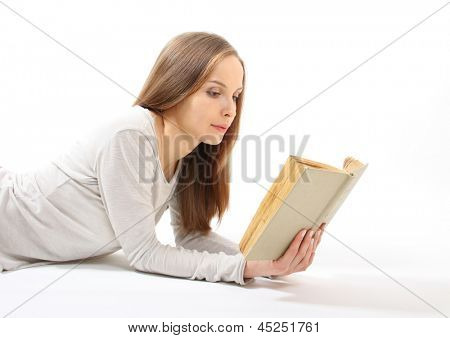 Lying girl with a book on white background