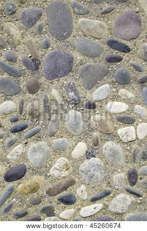 Stones embedded in concrete with loose pebbles