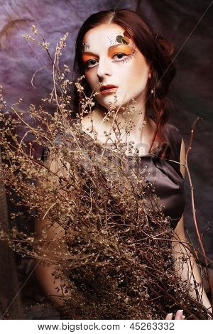 Young woman with bright make up with dry branches