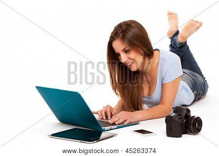 Junge caucasian Frau mit elektronischen Geräten, die auf einen weißen Boden liegend