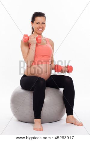 Beautiful pregnant woman working out with dumbbells isolated over white background