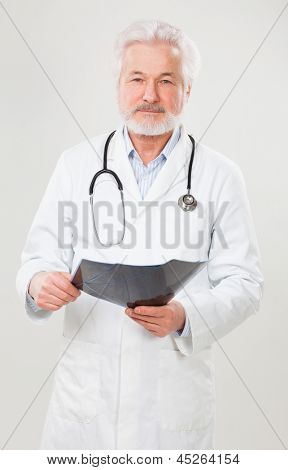 Handsome elderly doctor with radiograph over background