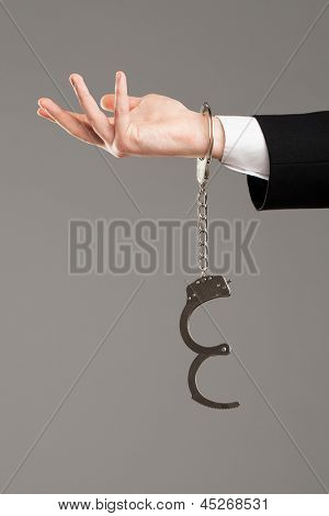 Businessman hand with opened handcuffs over grey background