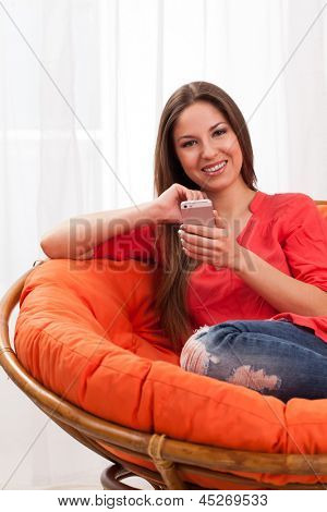 Beautiful woman holding smartphone sitting in orange chair