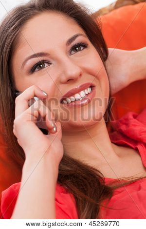 Young attractive woman calling by phone siiting in orange chair