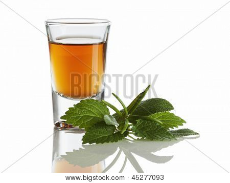 herbal liquor in shot glass and herbs isolated on white background