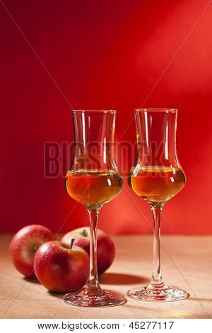 Two glasses of Calvados Brandy and red apples