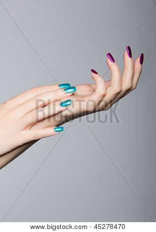blue and pink trend manicure on acrylic nails of a young Caucasian woman. close-up of the hand on a gray studio background