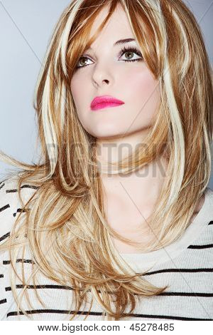 beautiful young woman with long blond hair wearing stripe top and bright pink lipstick on studio background