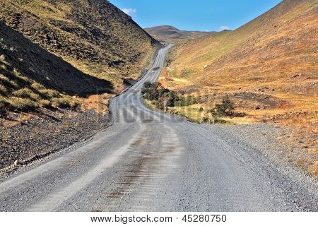 A gravel road winds among the hills and mountains.  Chilean Patagonia. Summer in the national park Torres del Paine