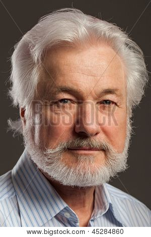 Closeup portrait of elderly man with beard on a black background