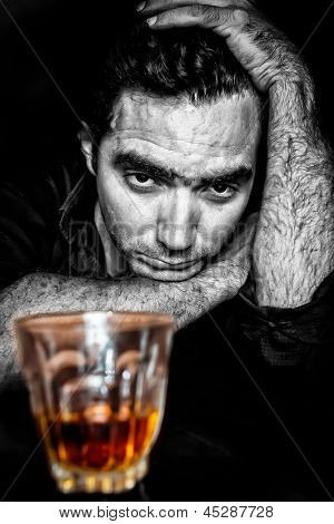 Black and white grunge portrait of a drunk and depressed hispanic man (with a contrasty golden alcoholic drink)