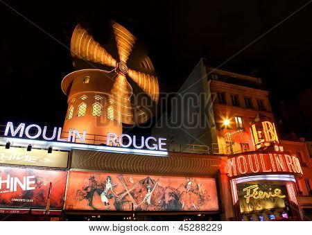 PARIS - APRIL 19: The Moulin Rouge at night, on April 19, 2013 in Paris, France. Moulin Rouge is a famous cabaret built in 1889, located in the Paris red-light district of Pigalle.