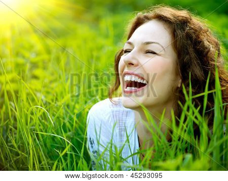 Beautiful Young Woman Outdoors. Enjoy Nature. Healthy Smiling Girl in Green Grass.