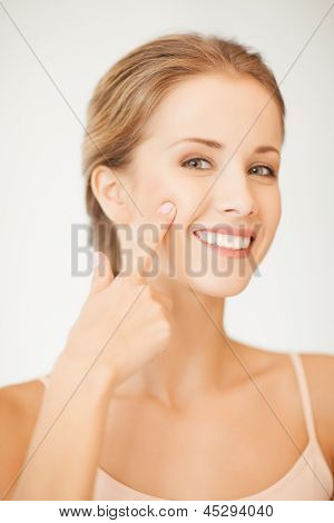 face of beautiful woman pointing at her cheek