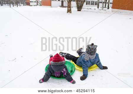 Children Sitting On The Slides Weary After Ride