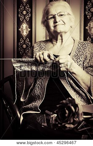 Portrait of a smiling senior woman knitting on spokes at home. Old-fashioned style.