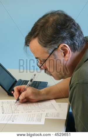 Man Doing 1040 Federal Income Tax Form