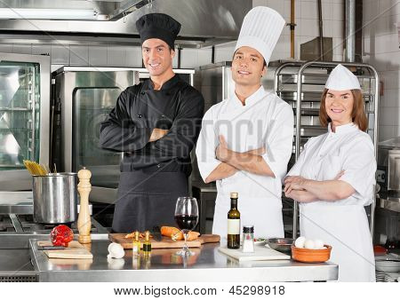 Portrait of confident chefs standing with arms crossed by kitchen counter