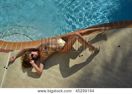 Fashion model posing pretty by swimming pool