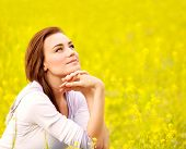 Closeup portrait of attractive brunette female sitting down on yellow floral field, rapeseed plantat