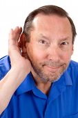 stock photo of hearing  - Senior man with a hearing loss cups his hand to his ear to help hear the sounds - JPG