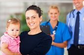 image of pediatric  - portrait of happy mother holding her baby girl in doctors office - JPG
