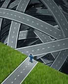 stock photo of edging  - Journey confusion and facing challenges with a businessman at the edge of a cliff in front of a group of tangled three dimensional roads and highwaysas a business concept of planning and managing adversity - JPG