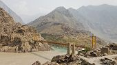 stock photo of karakoram  - Suspension bridge across the Indus River along the Karakorum Highway in Pakistan - JPG