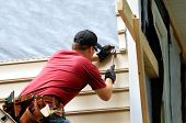 stock photo of tool  - Young homeowner installs siding to his home - JPG