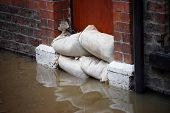 stock photo of flood  - Sandbag barrier in doorway of flooded street in York - JPG