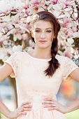 foto of magnolia  - beautiful smiling woman and pink magnolia outside in spring - JPG